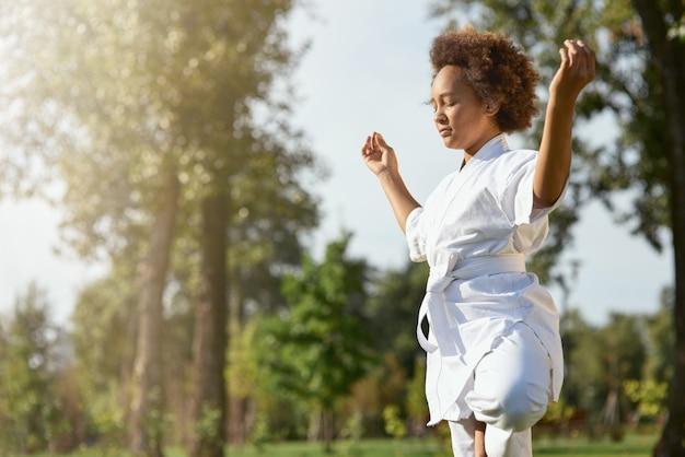 Serena garota afro-americana de quimono meditando ao ar livre