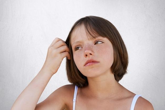 Séria criança sardenta, mantendo a mão no cabelo, tendo expressão pensativa, olhando de lado. linda garota posando contra parede branca. beleza, infância, conceito de expressão facial