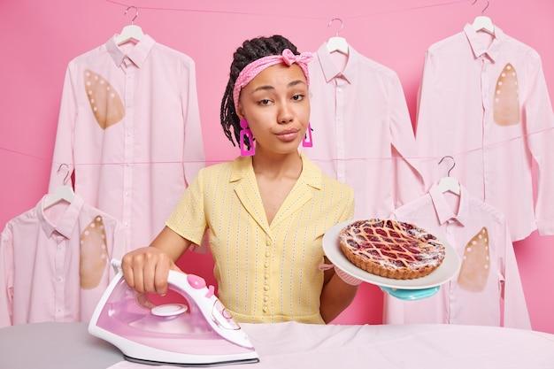 Séria dona de casa autoconfiante usa bandana, ferros de roupas domésticas, lavanderia, faz poses de torta deliciosas em roupão. processo de limpeza