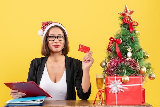 Séria e encantadora senhora de terno com chapéu de papai noel e óculos mostrando o cartão do banco no escritório em amarelo isolado