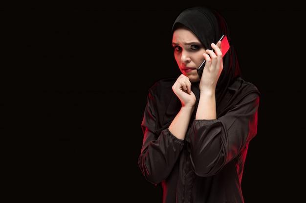 Séria mulher muçulmana nova assustada bonita vestindo preto hijab pedindo ajuda