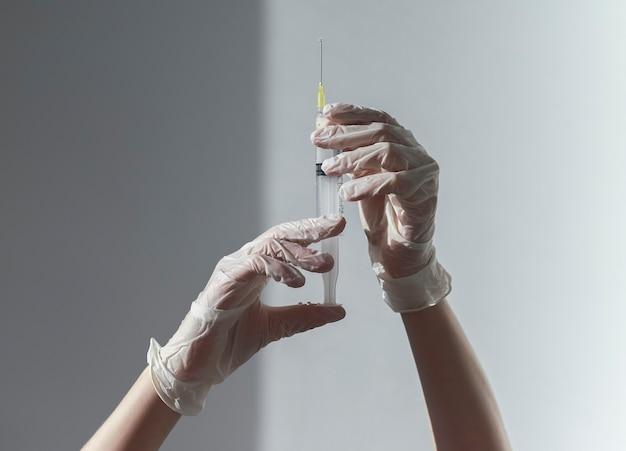 Seringa com agulha nas mãos do médico em luvas brancas
