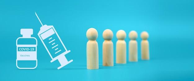 Seringa com agulha para vacina covid-19 de close-up e boneca de madeira de pessoas.