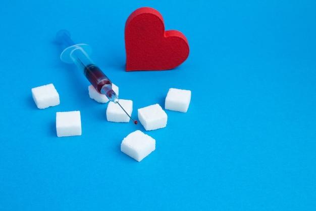 Seringa com sangue, açúcar e coração vermelho no azul