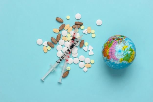 Seringa, comprimidos e globo na superfície azul. vacinação global. pandemia do covid19. vista do topo