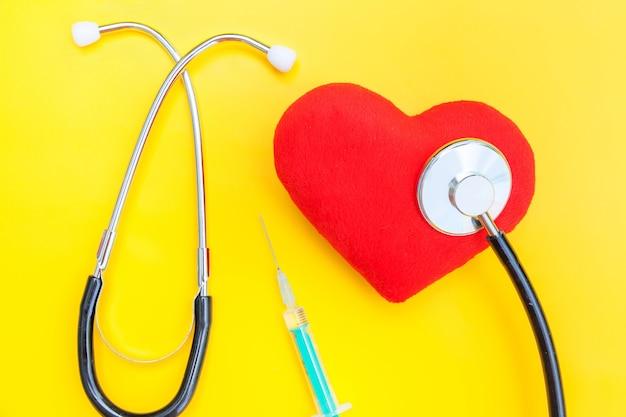 Seringa de estetoscópio de equipamentos de medicina e coração vermelho isolado na mesa amarela