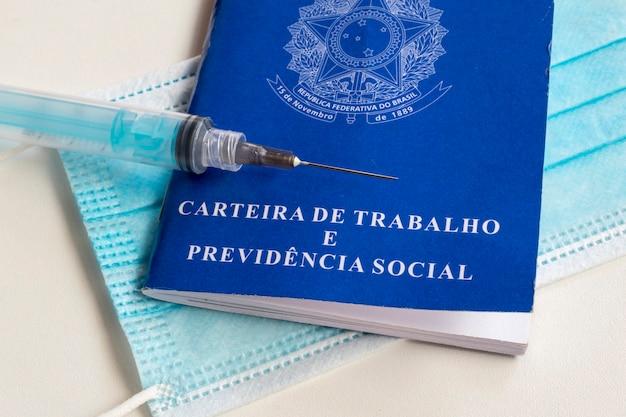 Seringa de vacina, máscara de proteção facial e carteira de trabalho brasileira.