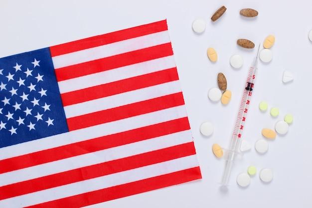 Seringa e comprimidos com a bandeira dos estados unidos da américa. vacinação