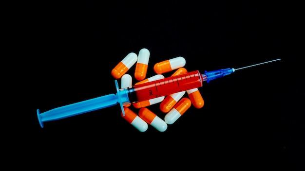 Seringa e comprimidos em um fundo preto isolado. conceito de vacinação.