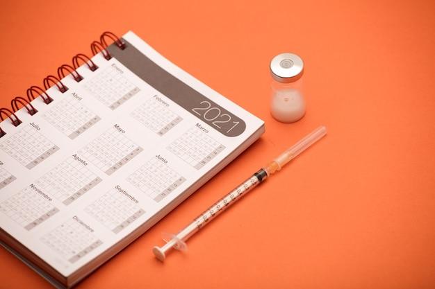 Seringa e vasilha de vacina, com calendário 2021, fundo laranja