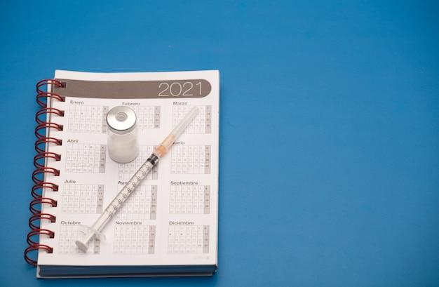 Seringa e vasilha de vacina, com calendário 2021, superfície azul