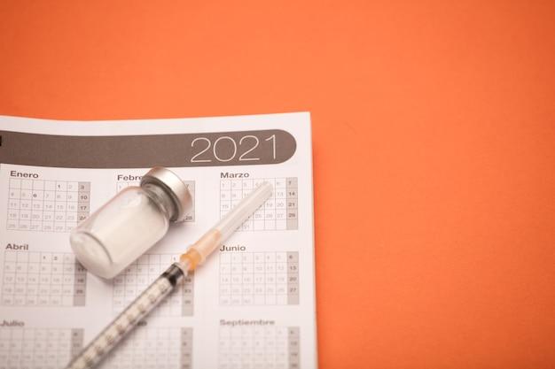 Seringa e vasilha de vacina, com calendário 2021, superfície laranja