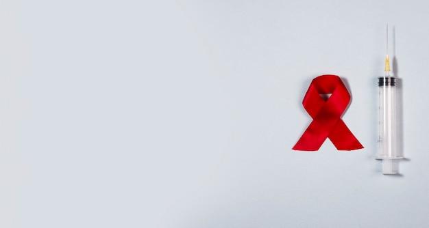 Seringa limpa e laço de fita vermelha como símbolo de aids e banner médico do dia da conscientização do hiv
