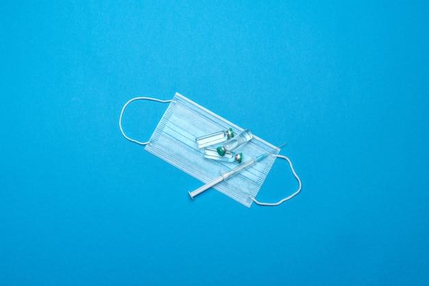 Seringa, máscara médica protetora e ampolas com medicamentos ou vacina sobre azul