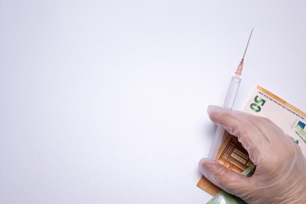 Seringa médica com vacina covid19 e fundo branco de dinheiro espaço livre para texto