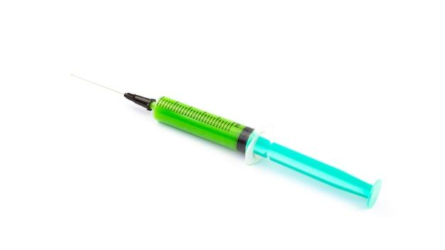 Seringa médica com vacina verde sobre fundo branco isolado. conceito de controle de vírus. vacinação da população.