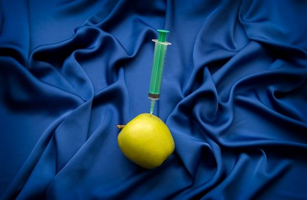 Seringa médica e maçã em um azul