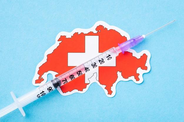 Seringa na bandeira da suíça sobre fundo azul. conceito de vacinação contra o coronavírus bem-sucedida na suíça