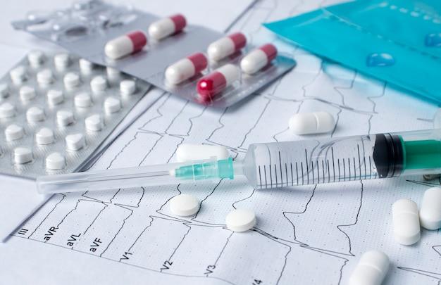 Seringa para injeção, medicamentos para o coração, cardigrama cardíaco. o conceito de diagnóstico de doenças cardiovasculares,