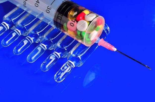 Seringa para injeções subcutâneas com ampolas de vidro e comprimidos multicoloridos