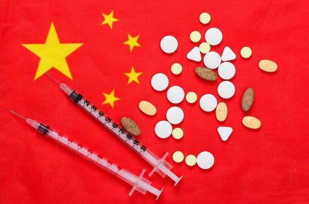 Seringas e comprimidos com bandeira da china. vacinação. pandemia covid-19