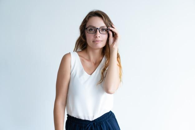 Sério bela dama, ajustando os óculos e olhando para a câmera