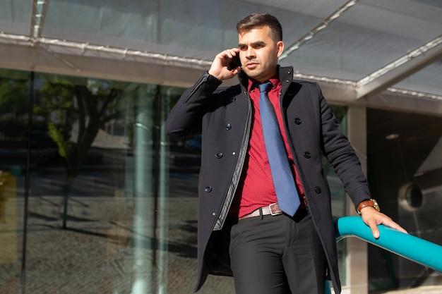 Sério, bonito, homem negócios, em, casaco preto, falando telefone