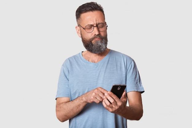 Sério cara morena calma olha atentamente de lado, segurando o telefone inteligente na mão, digitando mensagens para seus amigos, confuso sobre a postagem. modelo bonito, vestindo camiseta casual e especificações da moda.