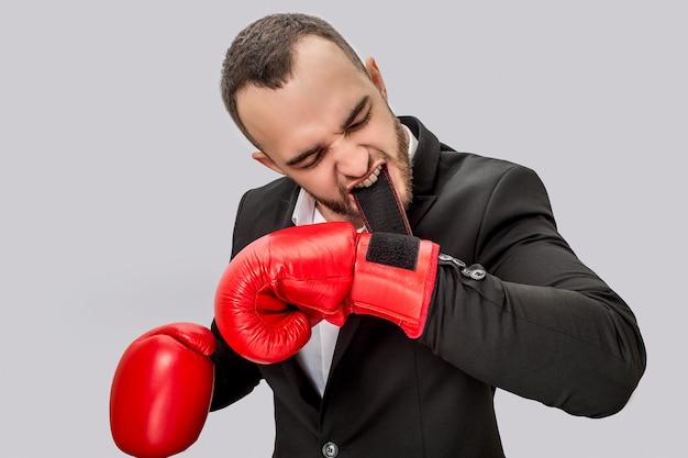 Sério e bravo jovem se preparando para lutar. ele segura o fecho na boca. guy está concentrado. ele usa terno e luvas de caixa vermelha.