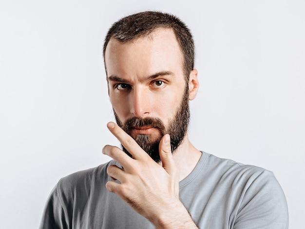Sério e intrigado modelo masculino bonito com barba segurando a mão no queixo como se estivesse pensando em algo, olhando para a câmera com olhar desconfiado e parado sobre uma superfície cinza