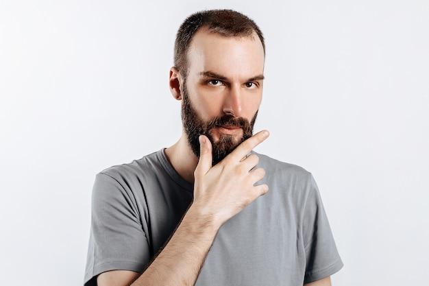 Sério e intrigado modelo masculino bonito com barba segurando a mão no queixo como se estivesse pensando em algo, olhando para a câmera com olhar suspeito e parado sobre uma superfície cinza