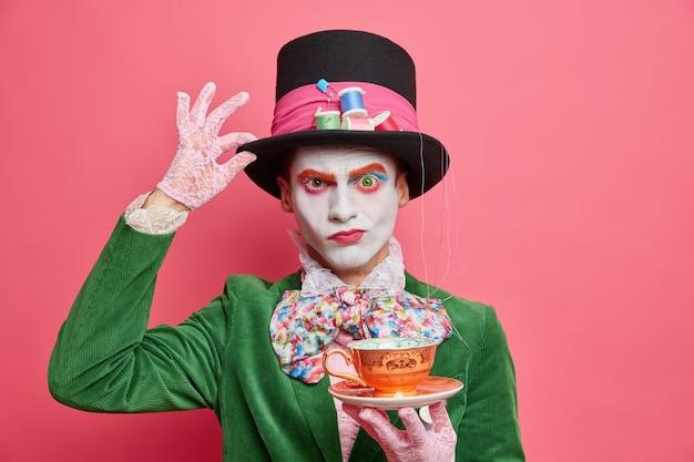 Sério e rigoroso chapeleiro masculino mantém a mão no chapéu alto, segurando uma xícara de chá no carnaval de halloween, com uma maquiagem profissional brilhante em uma parede rosada