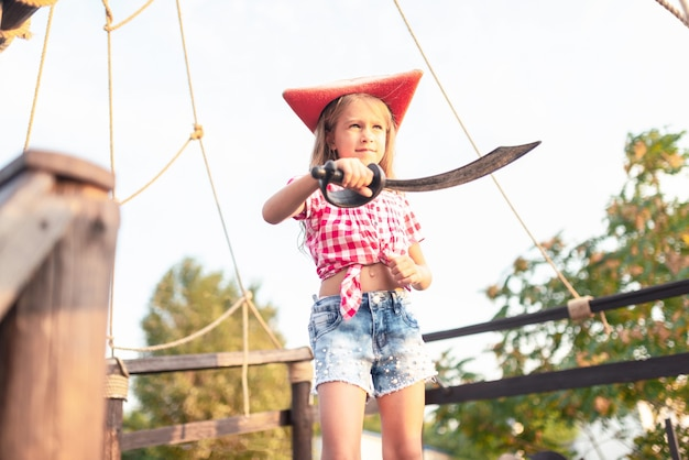 Sério engraçado menina pirata em uma camisa xadrez e shorts jeans segura as cordas do navio. crianças do conceito em busca de aventura