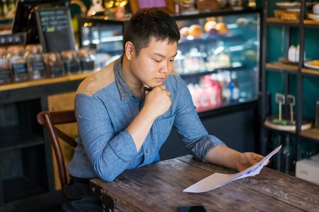 Sério homem concentrado escolhendo o almoço no café e aprendendo ofertas especiais