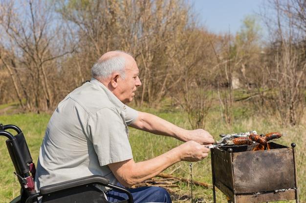 Sério homem idoso sentado em uma cadeira de rodas grelhar salsichas no parque em um dia muito ensolarado. capturado em vista lateral.