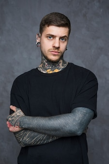 Sério homem jovem tatuado com piercing em seus ouvidos e nariz, olhando para a câmera