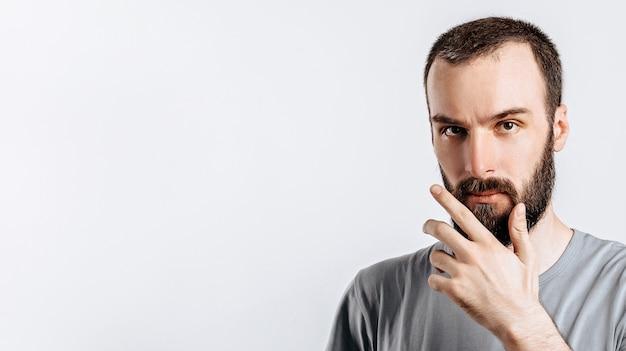 Sério intrigado modelo masculino bonito com barba segurando a mão no queixo como se estivesse pensando em algo, apertando os olhos para a câmera com olhar suspeito e de pé sobre um fundo cinza. homem decide o que comprar