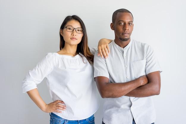 Sério jovem casal multiétnico confiante, olhando para a câmera e em pé no estúdio