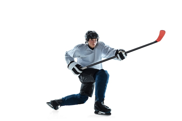 Sério. jovem jogador de hóquei com o taco na quadra de gelo e fundo branco. desportista usando equipamento e praticando capacete. conceito de esporte, estilo de vida saudável, movimento, movimento, ação.