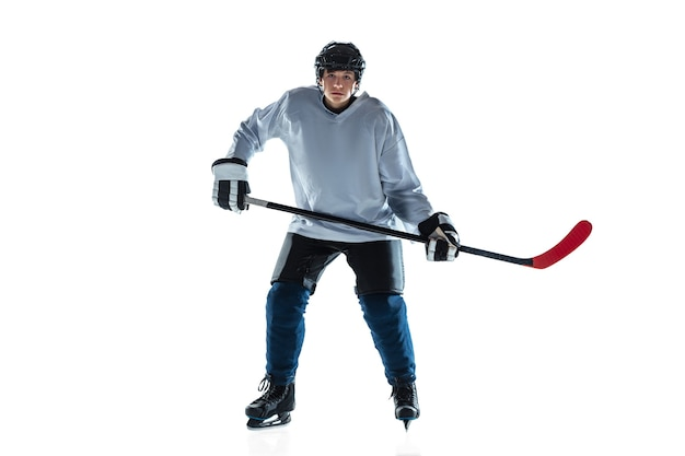 Sério. jovem jogador de hóquei com o taco na quadra de gelo e uma parede branca. desportista usando equipamento e praticando capacete. conceito de esporte, estilo de vida saudável, movimento, movimento, ação.