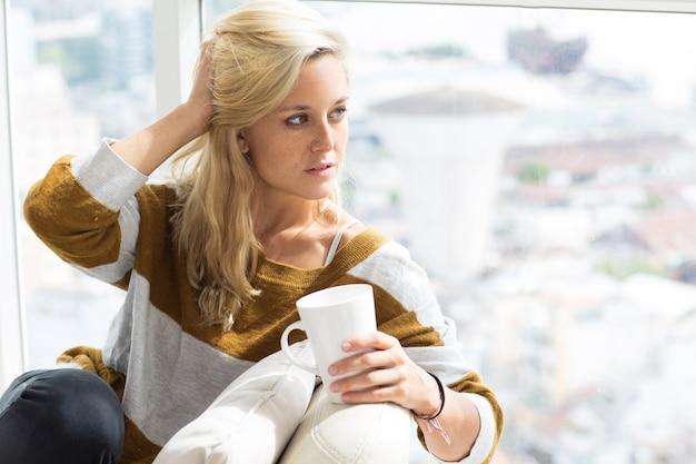 Sério jovem sentada em casa com xícara de chá