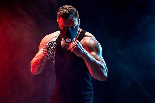 Sério lutador muscular fazendo o soco com as correntes trançadas sobre o punho.