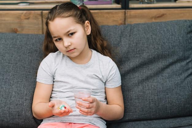 Sério menina sentada no sofá segurando pílulas e copo de água na mão