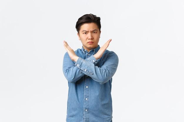 Sério preocupado estudante masculino asiático mostrando gesto de proibição, fazendo cruz sinal para parar alguém, discordar e proibir a ação, dizendo não, basta, estar farto, fundo branco de pé.