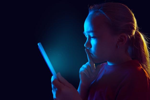 Sério. retrato da menina caucasiana isolado na parede escura em luz de néon. bela modelo feminino usando tablet. conceito de emoções humanas, expressão facial, vendas, anúncio, tecnologia moderna, gadgets.