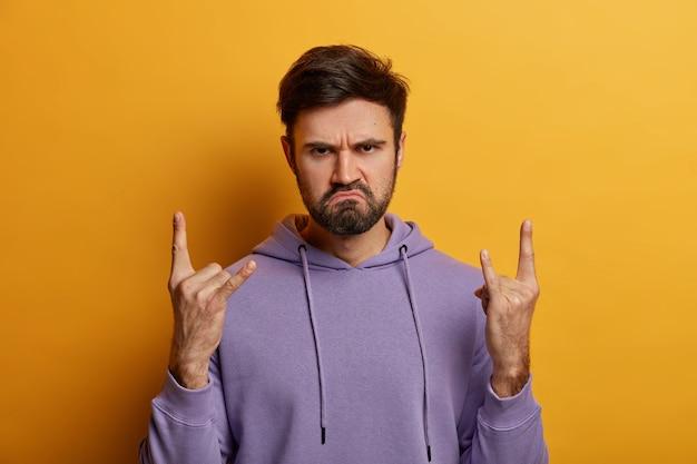 Sério roqueiro barbudo descontente faz sinal de chifre com os dedos, tem expressão facial carismática, rosto carrancudo, usa moletom roxo, vai a show de rock, isolado sobre parede amarela