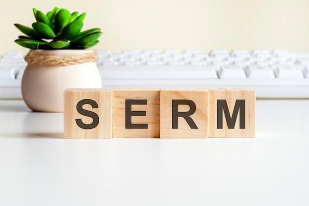 Sermo palavra feita com blocos de madeira. conceitos de vista frontal, planta verde em um vaso de flores e teclado branco no fundo