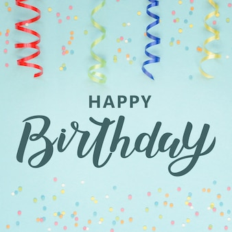 serpentina de decoração festiva colorfu e confetes sobre fundo azul. letras de feliz aniversário.