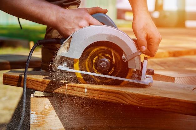 Serra circular. carpinteiro usando serra circular para viga de madeira