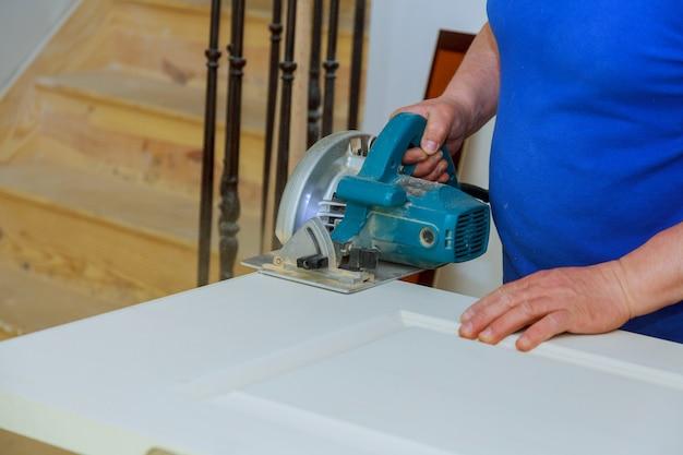 Serra circular para cortar a porta de madeira nas mãos do construtor